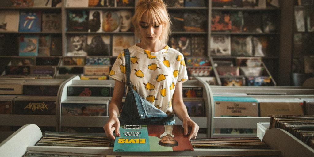 Frau mit blondem Zopf, einem T-Shirt und lockerer Latzhose steht an einem Schallplatten-Stand und schaut sich eine Schallplatten Hülle von Elias an